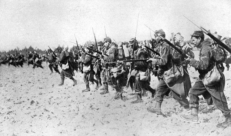 Długi szereg żołnierzy biegnących z karabinami w rękach. Na karabinach widoczne bagnety.