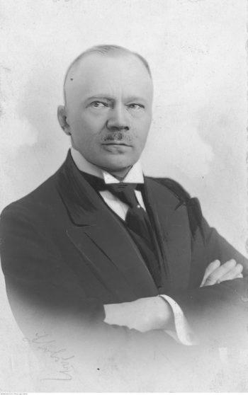 Portret mężczyzny w średnim wieku o surowym spojrzeniu i skrzyżowanych na piersi rękach. Ubrany w czarny garnitur, białą koszulę i krawat, ma krótko ostrzyżone włosy i krótki wąs.