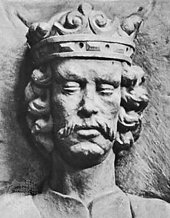 Rzeźba przedstawiająca wąską twarz wąsatego mężczyzny o kręconych włosach sięgających szyi. Na jego głowie spoczywa korona otwarta.