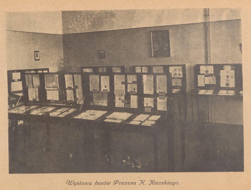 Czarno-białe zdjęcie przedstawiające salę z dwoma rzędami gablot, w których widoczne są karty dokumentów.